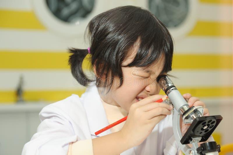 azjatykciego dzieciaka przyglądający mikroskop fotografia royalty free