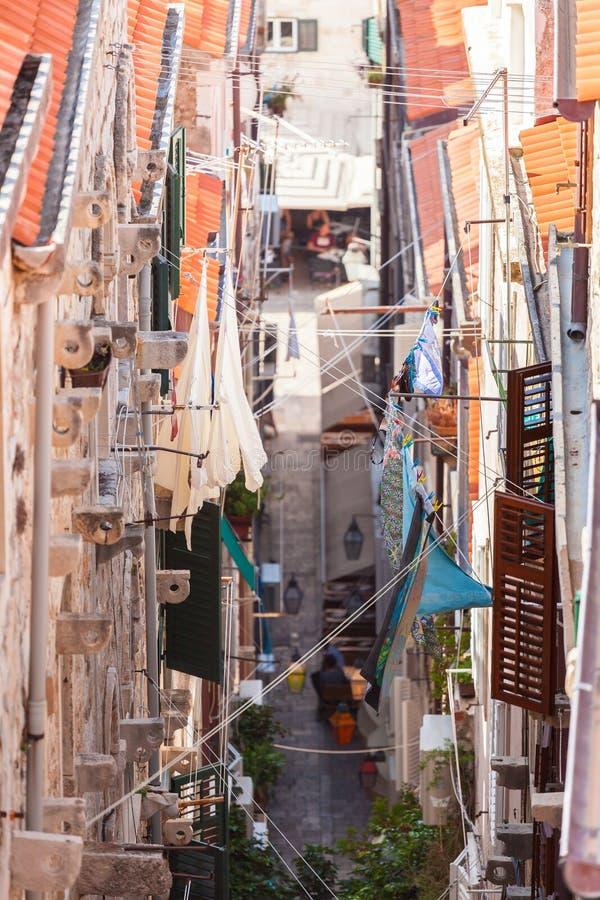 Azoteas viejas de la ciudad de Dubrovnik Silueta del hombre de negocios Cowering Liquidación a través de las calles estrechas de  fotos de archivo