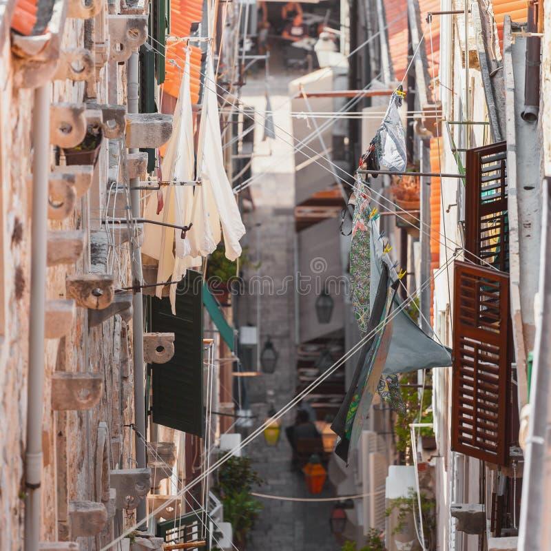 Azoteas viejas de la ciudad de Dubrovnik Silueta del hombre de negocios Cowering Liquidación a través de las calles estrechas de  fotografía de archivo libre de regalías