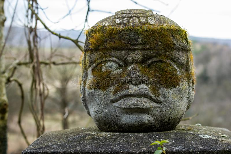 The Aztec statue on a pylon. The head or face is made from stone and covered with moss royalty free stock images