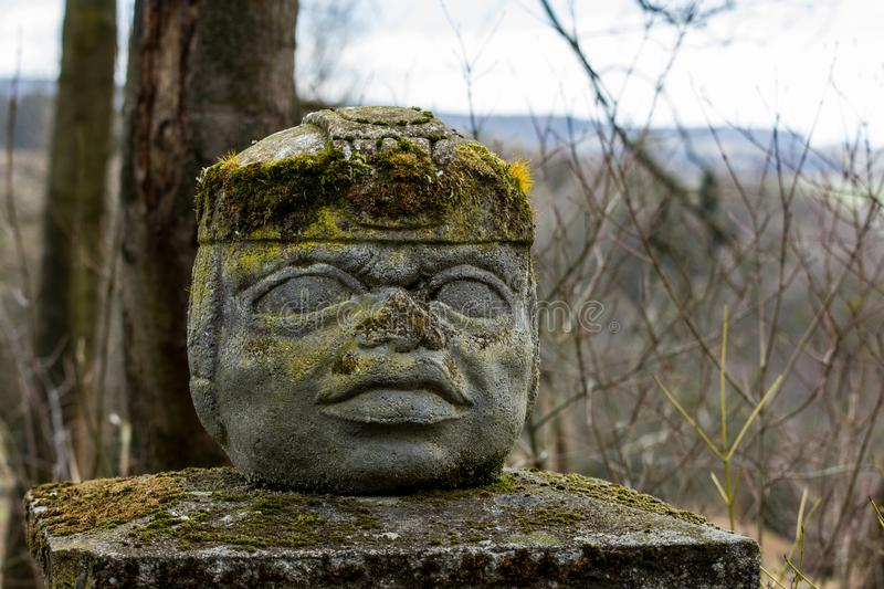 The Aztec statue on a pylon. The head or face is made from stone and covered with moss royalty free stock photos