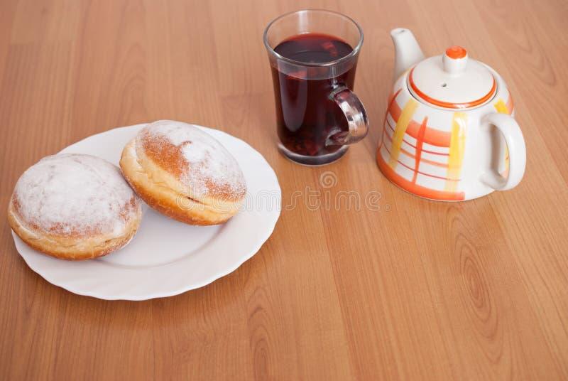 Azucare buñuelos revestidos, un vidrio de té de la fruta y el pote del té en la placa blanca en fondo de madera marrón imágenes de archivo libres de regalías