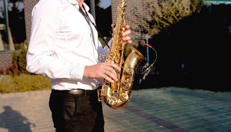 Azuis dourados Os meninos unem a seção no evento, homem do saxofone do jogador do jazz que joga no saxofone, instrumento de músic foto de stock