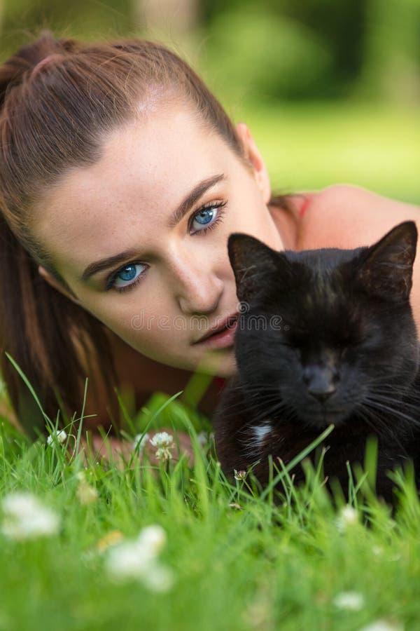 Azul bonito adolescente fêmea Eyed da menina com gato preto fotos de stock
