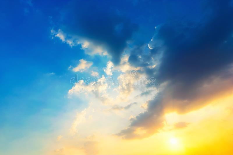 Azul-céu e luz alaranjada do sol através das nuvens no céu fotos de stock