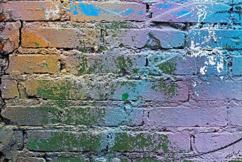 Azul colorido, púrpura abstracto, anaranjado, blanco y verde pintaron la pared de ladrillo fotos de archivo