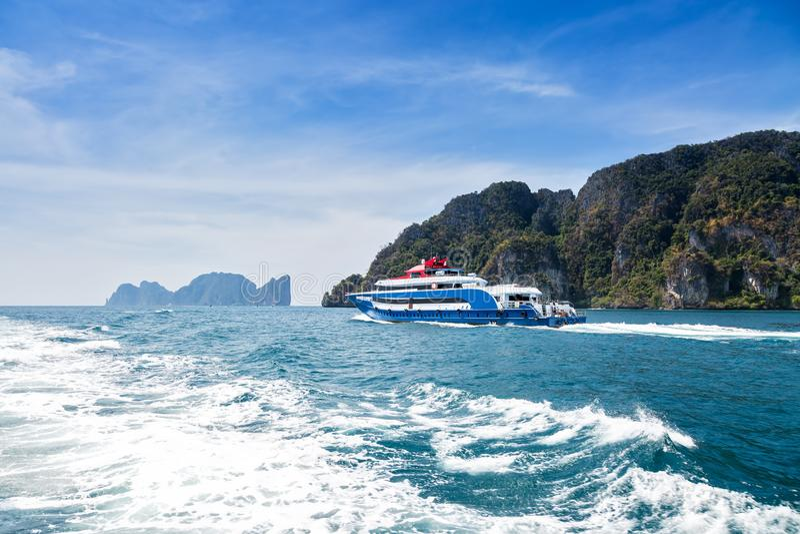 Azul com o barco branco e vermelho da velocidade do prazer dos acentos Navigação no mar contra uma ilha tropical Vista traseira T fotografia de stock royalty free