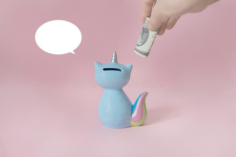 Azul de cerámica de Korn del gatito de la caja de dinero del juguete del recuerdo con la cola colorida del arco iris con el cuern foto de archivo libre de regalías