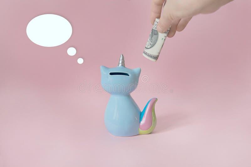 Azul de cerámica de Korn del gatito de la caja de dinero del juguete del recuerdo con la cola colorida del arco iris con el cuern foto de archivo