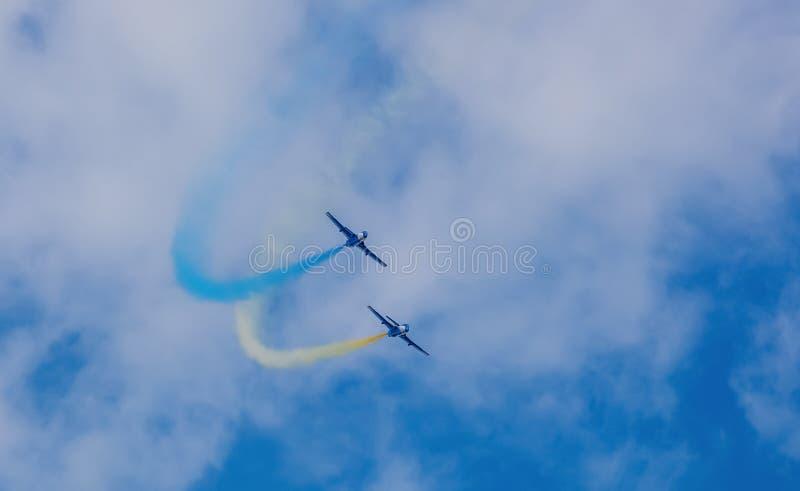 Azul de dois aviões durante um desempenho em uma tira do fumo do produto do conluio do airshow de azul e de amarelo no céu imagem de stock royalty free