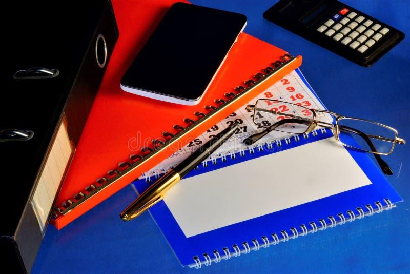 Azul de escritorio del fondo de la oficina que considera, con los accesorios necesarios, el cálculo de impuestos, costos y renta  foto de archivo