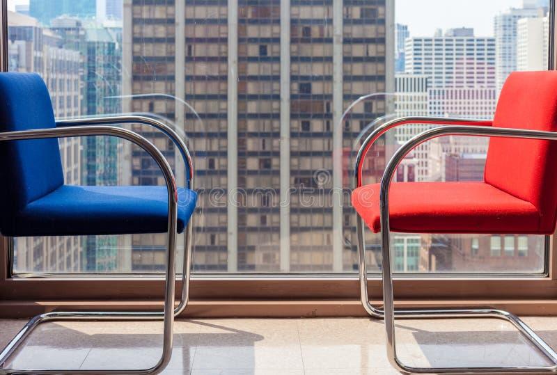 Azul e cadeiras de espera vermelhas contra a janela completa do comprimento com arquitetura da cidade no fundo foto de stock