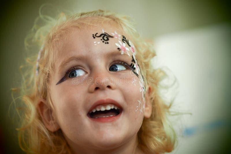 Azul louro pequeno a pintura eyed da cara da menina está sorrindo imagens de stock royalty free