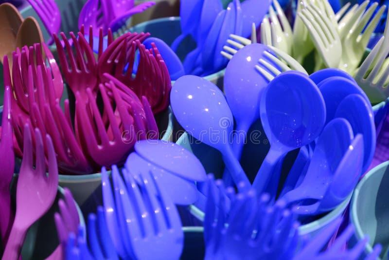 Azul vivo del primer y bifurcaciones y cucharas plásticas de las mercancías de los colores púrpuras en tazas plásticas fotos de archivo libres de regalías