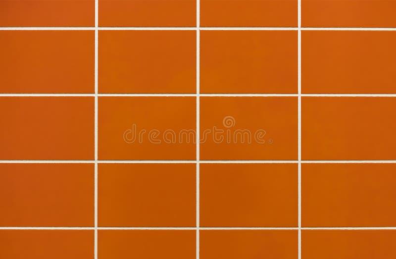 Azulejo alaranjado na parede no banheiro Fundo das telhas alaranjadas imagem de stock