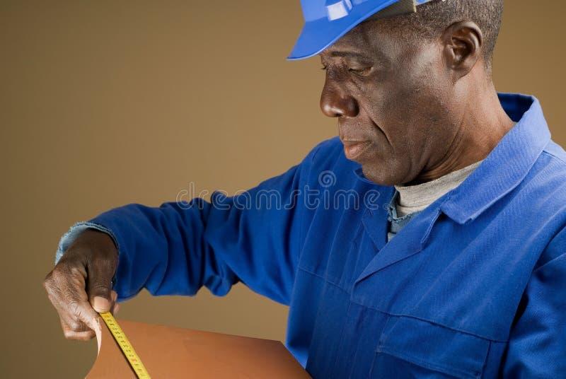 Azulejo de medición del trabajador de construcción fotos de archivo libres de regalías