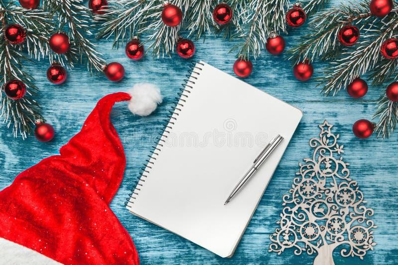 Azur bakgrund, tabellen för arbete för jultomten` s, gåvalistan, granfilialer smyckade med röda jordklot Top beskådar royaltyfri bild