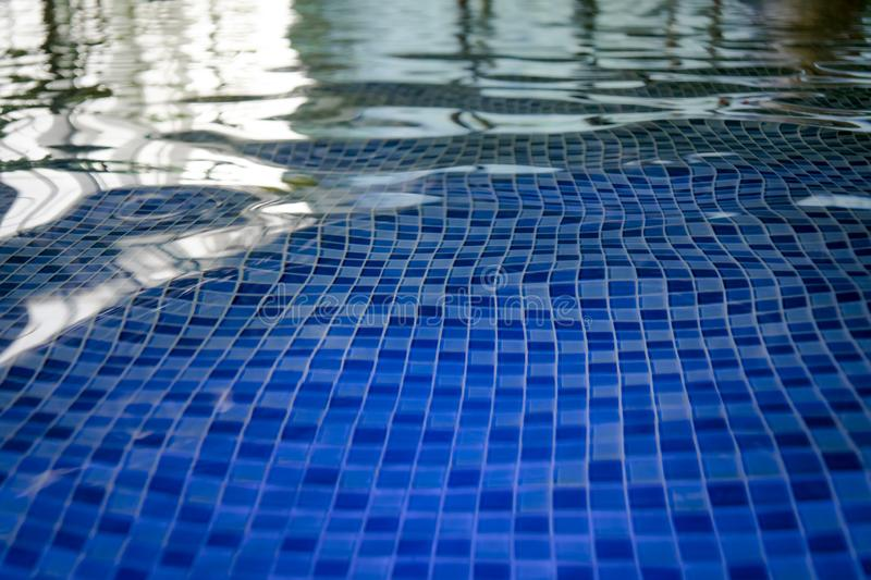 The azur mosaic bottom of an aquapark pool. A view to the tiled floor through the clean water of indoor pool. Ripples and blinks o stock photography
