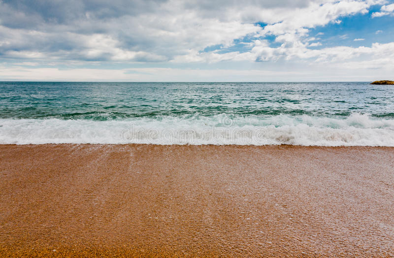 Azure calm sea with orange beach. And cloudy blue sky. Low angle, wide view on straight front. Horizontal ful frame crop royalty free stock image