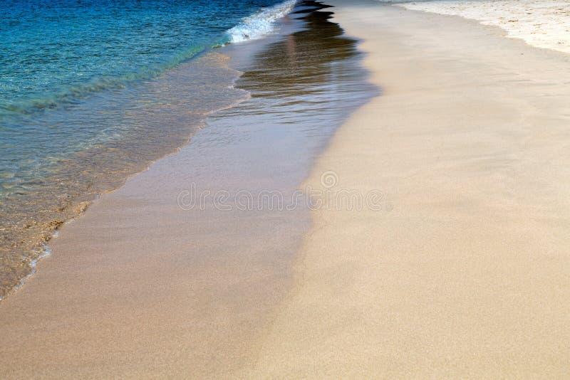 Azuurblauw water en geel zand, close-upgolf royalty-vrije stock afbeeldingen