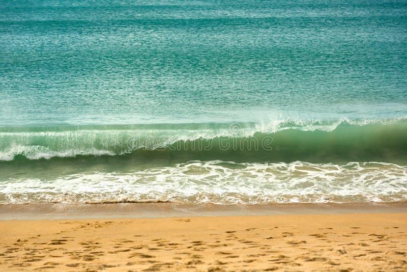 Azuurblauwe golf op het strand stock afbeeldingen