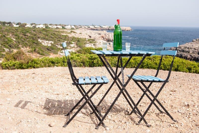 Azuurblauwe lijst en stoelen in een panoramisch punt van Menorca stock afbeeldingen