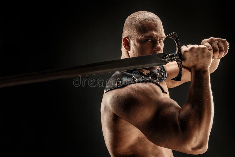 Bárbaro severo no traje de couro com espada imagem de stock royalty free