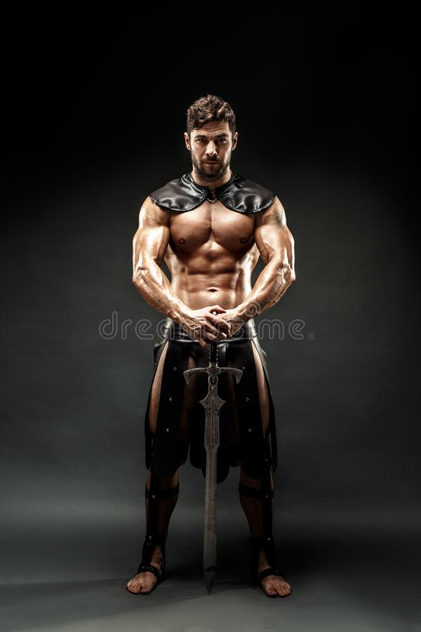 Bárbaro severo no traje de couro com espada imagens de stock