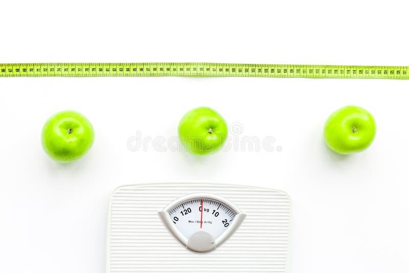 Báscula de baño, cinta métrica y manzanas en la opinión superior del fondo blanco fotografía de archivo