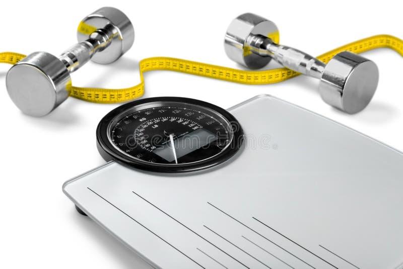 Báscula de baño con una cinta métrica y pesas de gimnasia imagen de archivo libre de regalías