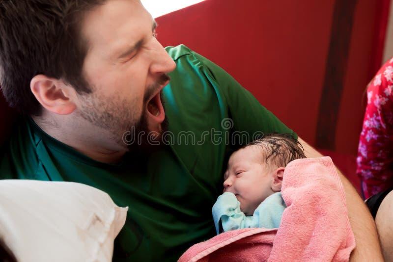 Bâillements de papa tout en tenant son fils nouveau-né images stock