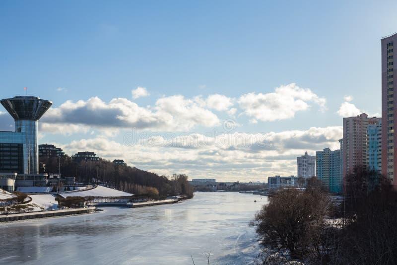 Bâtiment étonnant sur les banques de la rivière couverte de la glace image libre de droits