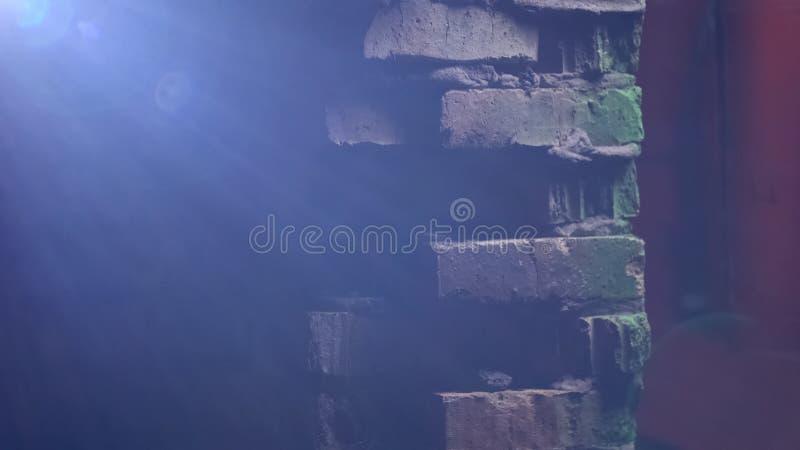 Bâtiment abandonné dans la ruelle foncée avec le symbole de soleil lumineux, d'espoir et de foi photographie stock