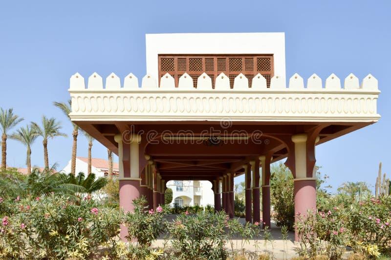 Bâtiment en pierre blanc avec le style latin mexicain de colonnes sur le fond des palmiers tropicaux exotiques de plantes vertes  image libre de droits