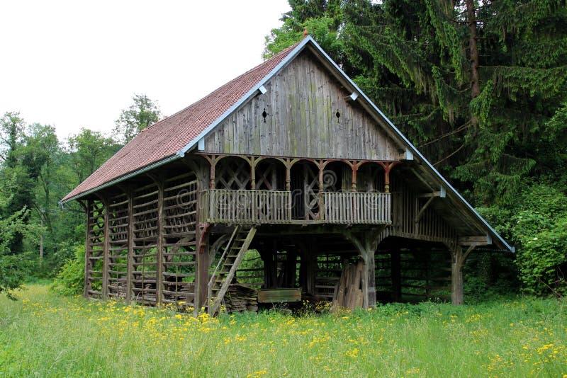 Bâtiment extérieur de vieille grange en bois entouré avec la hautes herbe et fleurs photographie stock