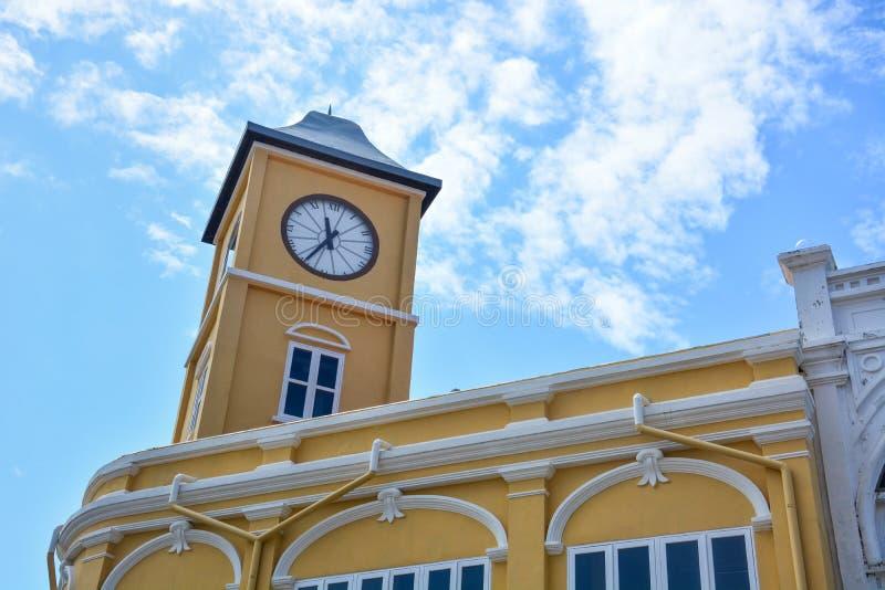 Bâtiment jaune avec la tour d'horloge dans le style Chino-portugais sur le fond de ciel bleu, vieille ville de Phuket, Thaïlande photo stock