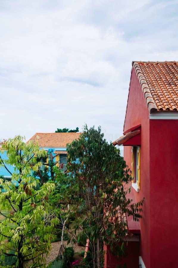 Bâtiment méditerranéen coloré de style avec le grand jardin d'arbre images stock