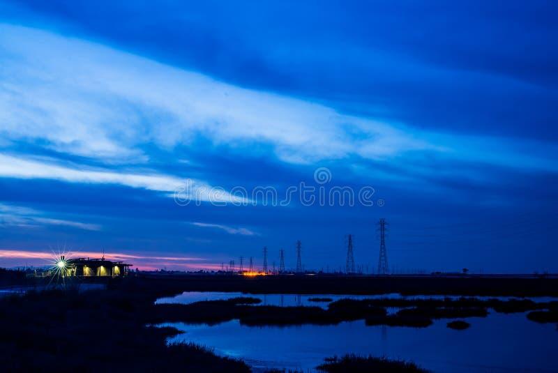 Bâtiment, mer et pylônes bleus - coucher du soleil photographie stock libre de droits