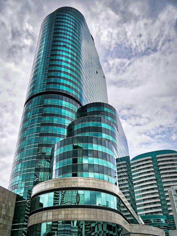 Bâtiment moderne de vert bleu contre le ciel nuageux bleu image libre de droits