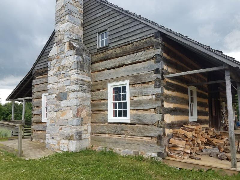 Bâtiment ou carlingue en bois avec le bois de chauffage et la cheminée de pierre image libre de droits