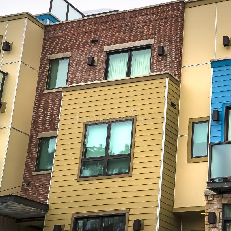 Bâtiment résidentiel de cadre carré avec le béton de dégrossissage horizontal et brique sur le mur photo stock
