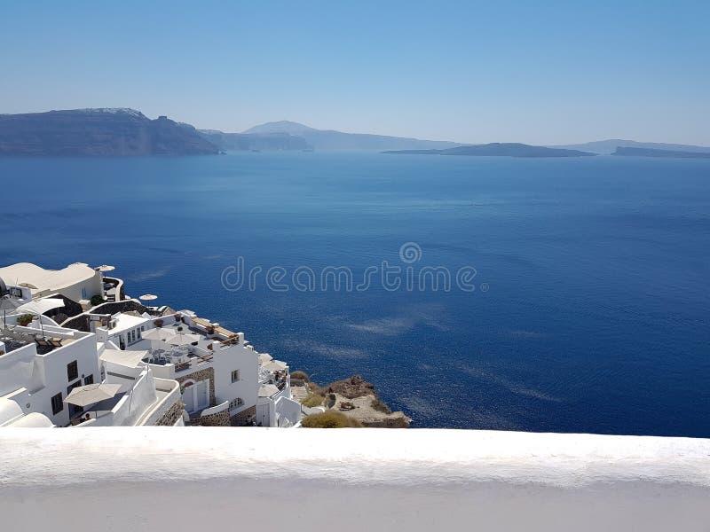 Bâtiments blancs en Santorini et mer ouverte photo stock