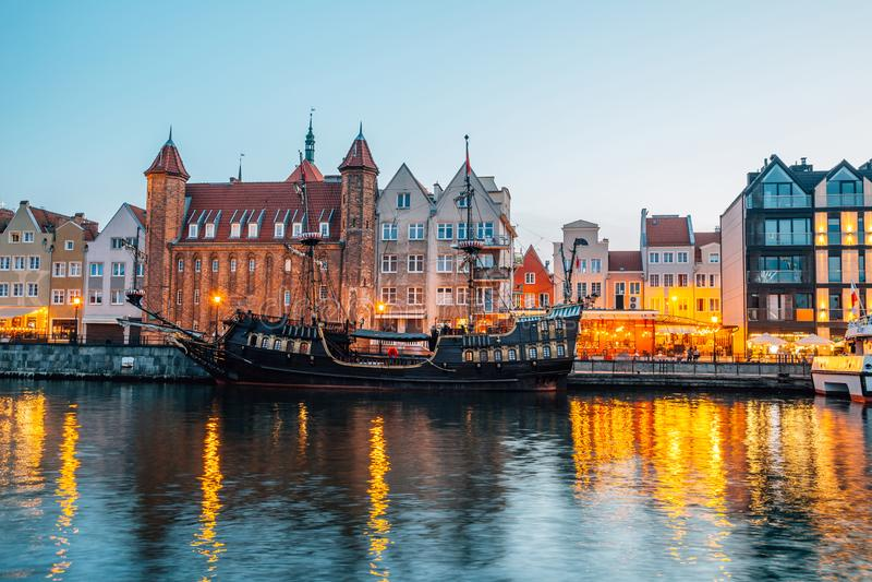Bâtiments de la vieille ville et porte de Straganiarska avec rivière la nuit à Gdansk, Pologne photos stock