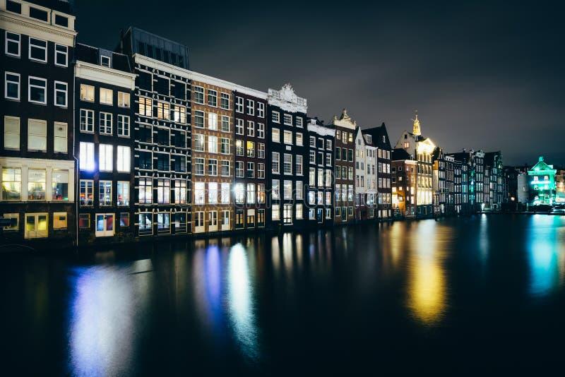 Bâtiments le long du canal de Damrak la nuit, à Amsterdam, le filet photos libres de droits