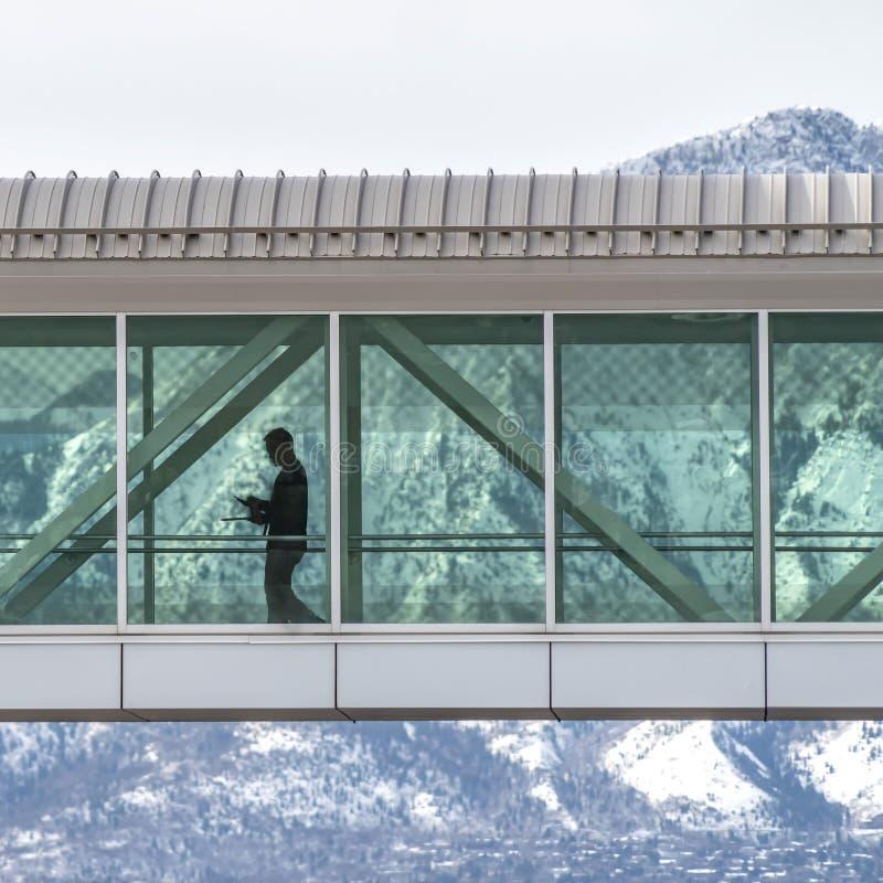 Bâtiments se reliants de Skyway de place avec un fond de montagne neigeuse et de ciel nuageux photographie stock libre de droits