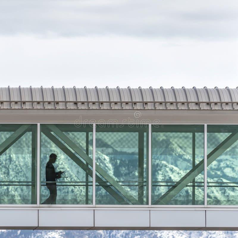 Bâtiments se reliants de Skyway de place claire avec un fond de montagne neigeuse et de ciel nuageux image stock