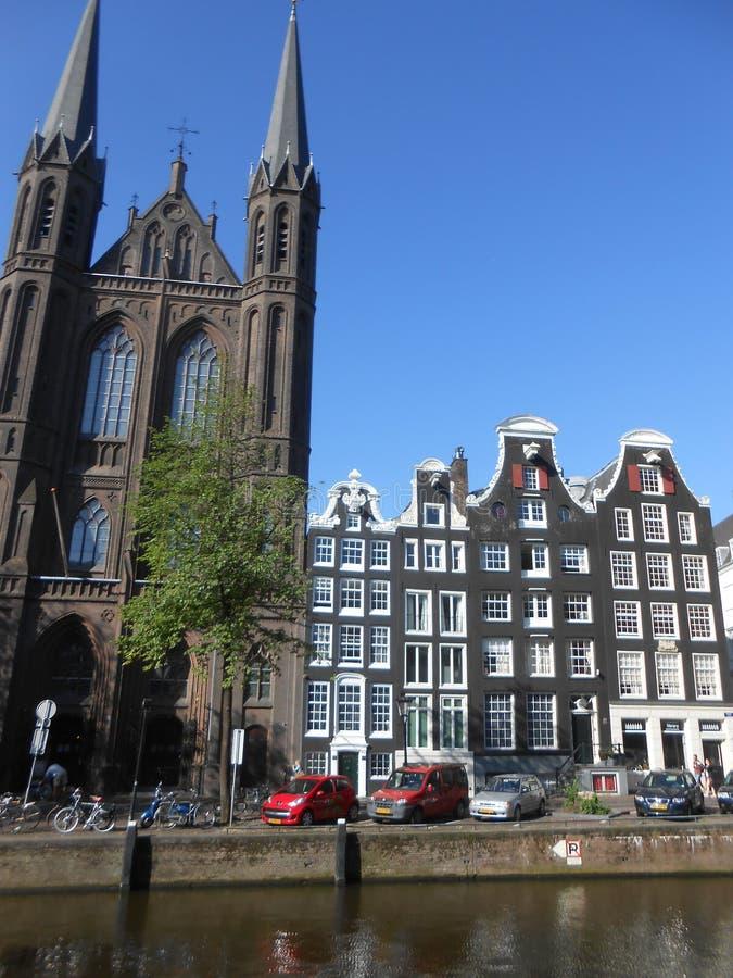Bâtiments typiques et une église, sur les canaux d'Amsterdam photos stock