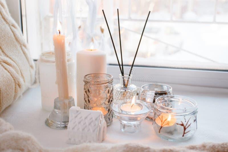 Bâton d'arome près de fenêtre avec des bougies pendant le matin, fond monochrome clair confortable de ressort d'hiver photo stock
