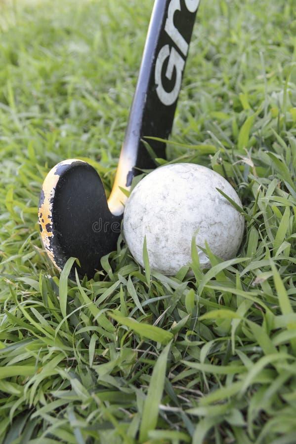Bâton de hockey et boule usés de champ images libres de droits