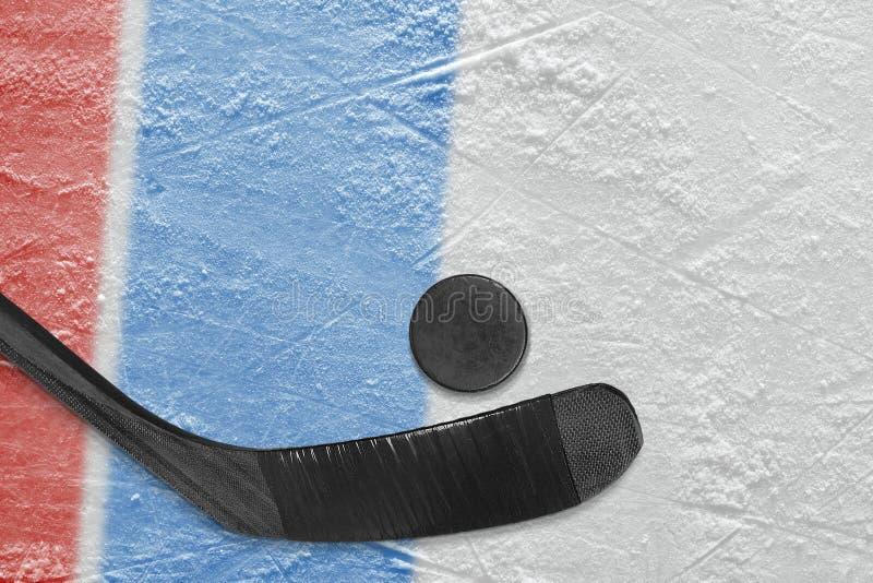 Bâton de hockey, galet et fragment de l'arène de glace avec le bleu et le r photos stock